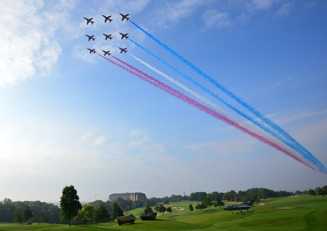 Britain's Red Arrows airplane display team perform a flypast over the NATO 2014 Summit at the Celtic Manor Hotel in Newport, South Wales, on September 5, 2014. NATO leaders are expected to announce a raft of fresh sanctions against Russia on Friday over its actions in Ukraine, although hopes remain that a ceasefire can be forged at peace talks in Minsk on the same day. (Photo by Carl Court/AFP Photo)