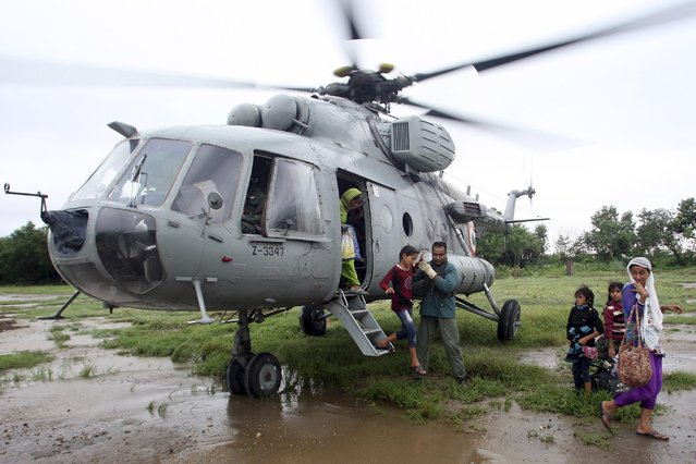 An Indian Air Force personnel helps a flood victim girl to disembark from a MI-17 helicopter after she was evacuated during a rescue operation at a flooded area in Hamirpur Kona in Rajouri district, northwest of Jammu September 6, 2014. (Photo by Reuters/Indian Ministry of Defence)
