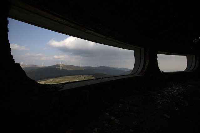 Power-generating windmill turbines are seen through the windows of the Memorial House of the Bulgarian Communist Party on mount Buzludzha September 12, 2014. (Photo by Stoyan Nenov/Reuters)