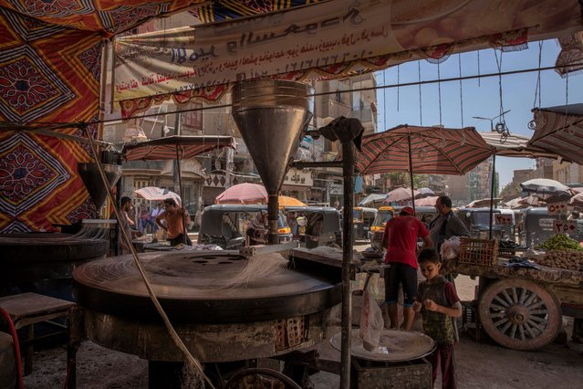 This May 9, 2020 photo, shows the Ramadan sweets shop where 28-year-old football defender Mahrous Mahmoud works at a market, in Manfalut, a town 350 kilometers (230 miles) south of Cairo, in the province of Assiut, Egypt. Mahmoud should be on the field at this time of year playing as a defender for Beni Suef, a club in Egypt's second division. But like millions in the Arab world's most populous country, he has been hit hard by the coronavirus pandemic. (Photo by Nariman El-Mofty/AP Photo)