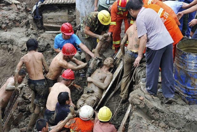 A worker (C) is rescued by colleagues and fire-fighters after he was trapped in a cave-in at a construction site in Wuhan, Hubei province, September 12, 2014. The 23-year-old worker, surnamed Feng, was doing measurement works early Friday morning in a foundation pit of the construction site while the cave-in occurred. (Photo by Reuters/Stringer)