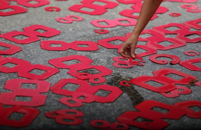 A woman lays cutouts of number 8 during the ceremony marking the 28th anniversary of the 8888 uprising in Yangon, Myanmar, 08 August 2016. The 08 August 1988, also known as '8888 Uprising' marked the start of protests by students in Yangon that would soon spread through the country. The demonstrations were aimed at the then ruling Burma Socialist Programme Party regime of the one-party state, headed by General Ne Win. The protests ended in September the same year after a military coup by the State Law and Order Restoration Council (SLORC). (Photo by Lynn Bo Bo/EPA)