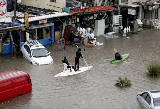 Lebanese men use a paddle board and canoe as means of transportation on a flooded road due to heavy rain, at the southern entrance of the capital Beirut on December 9, 2019. (Photo by Anwar Amro/AFP Photo)