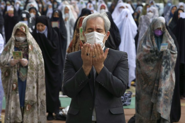 Worshippers wearing protective face masks offer Eid al-Fitr prayers outside a mosque to help prevent the spread of the coronavirus, in Tehran, Iran, Sunday, May 24, 2020. Muslims worldwide celebrate one of their biggest holidays under the long shadow of the coronavirus, with millions confined to their homes and others gripped by economic concerns during what is usually a festive time of shopping and celebration. In Iran, which has endured the deadliest outbreak in the Middle East, authorities have imposed few restrictions ahead of the holiday aside from cancelling mass prayers in Tehran traditionally led by Supreme Leader Ayatollah Ali Khamenei. (Photo by Vahid Salemi/AP Photo)