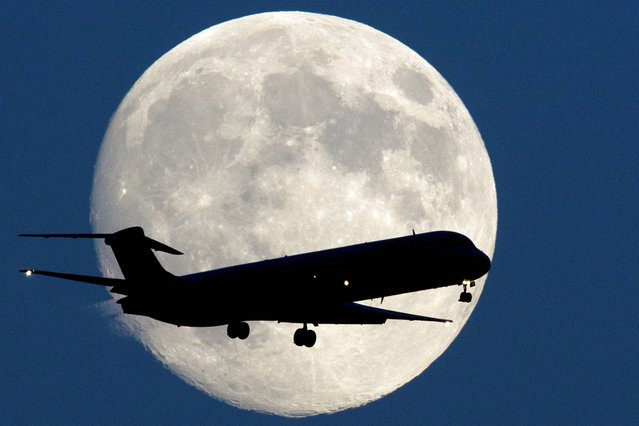 An airplane passes the moon as it makes its approach to Philadelphia International Airport, Sunday, September 7, 2014, in Philadelphia. (Photo by Matt Rourke/AP Photo)