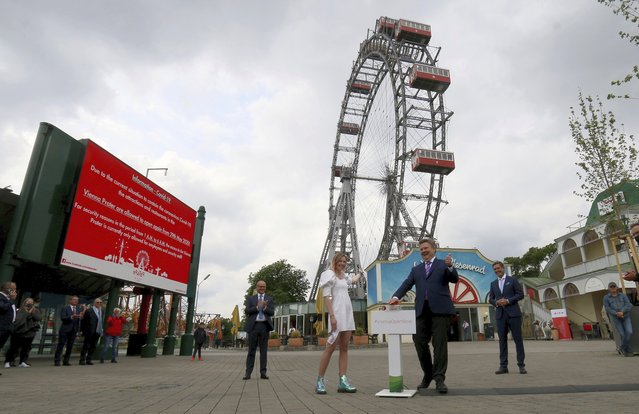 The Mayor of Vienna Michael Ludwig, center, presses a button to restarts the giant Ferris Wheel to symbolically signal the resumption of tourism in Austria in Vienna, Austria, Friday, May 29, 2020. Amusements are open again in Austria as part of relaxing the restrictions to slow the coronavirus and the COVID-19 disease. (Photo by Ronald Zak/AP Photo)