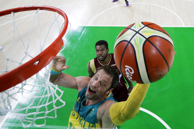 Australia's David Andersen drives to the basket past Venezuela's Nestor Colmenares, rear, during a basketball game at the 2016 Summer Olympics in Rio de Janeiro, Brazil, Sunday, August 14, 2016. (Photo by Charlie Neibergall/AP Photo)