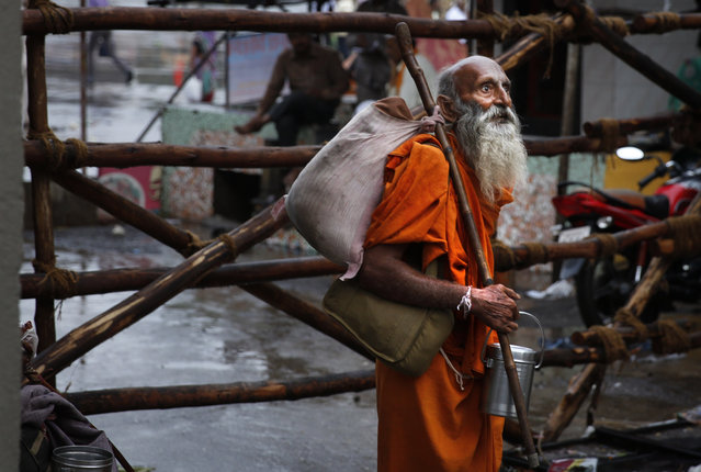 An Indian holy man looks at a temple after arriving in Nasik for the second holy bath in the Godavari River, during Kumbh Mela, or Pitcher Festival, India, Saturday, September 12, 2015. Hindus believe taking a dip in the waters of a holy river during the festival will cleanse them of their sins. According to Hindu mythology, the Kumbh Mela celebrates the victory of gods over demons in a furious battle over a nectar that would give them immortality. (Photo by Manish Swarup/AP Photo)