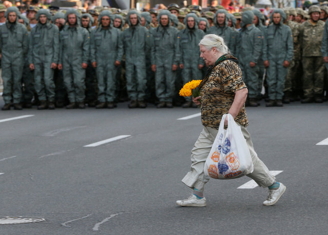 A woman crosses a street in front of Ukrainian servicemen during a rehearsal for the Independence Day military parade in central Kiev, Ukraine, August 22, 2016. (Photo by Valentyn Ogirenko/Reuters)