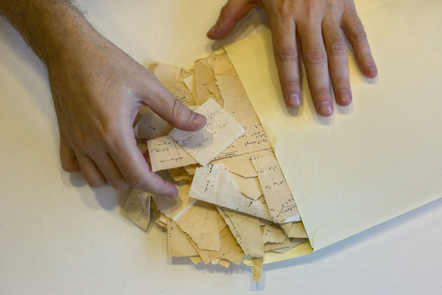"In this photo taken Sunday, October 5, 2014, a library official shows scraps from Israeli Nobel laureate S.Y. Agnon's masterpiece ""Shira"" at Israel's National Library in Jerusalem. (Photo by Sebastian Scheiner/AP Photo)"