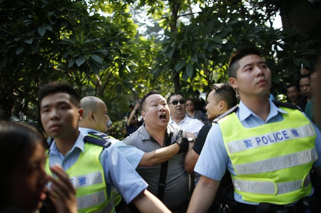 An anti-Occupy Central protester (C) shouts to pro-democracy protesters as he is dragged away by police officers at the main protest site in Admiralty in Hong Kong, October 13, 2014. (Photo by Carlos Barria/Reuters)