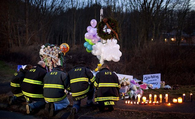 Firefighters kneel in front of a makeshift memorial for the victims of the Sandy Hook Elementary School shooting, near the school's entrance. Connecticut's chief medical examiner said Saturday it appeared that all of the children killed at the elementary school had been shot with a long rifle, as new and tragic details about the massacre of 26 people Friday emerged. (Photo by Marcus Yam/The New York Times)