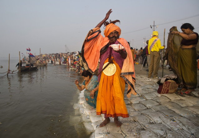 "A Sadhu, or a Hindu holy man, performs morning prayers on the banks of the river Ganges ahead of the ""Kumbh Mela"" (Pitcher Festival) in the northern Indian city of Allahabad January 13, 2013. During the festival, Hindus take part in a religious gathering on the banks of the river Ganges. ""Kumbh Mela"" will return to Allahabad in 12 years. (Photo by Ahmad Masood/Reuters)"