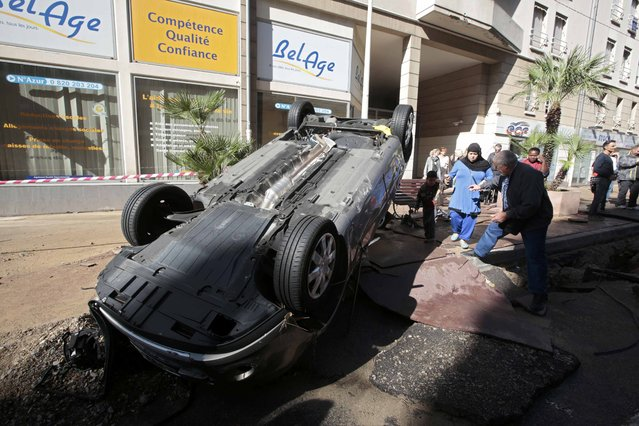 People look at an overturned car in the street that was damaged in flooding caused by torrential rain in Cannes, France, October 4, 2015. (Photo by Eric Gaillard/Reuters)