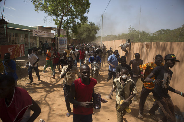 Anti-government protesters run from military gunfire in Ouagadougou, capital of Burkina Faso, October 30, 2014. (Photo by Joe Penney/Reuters)
