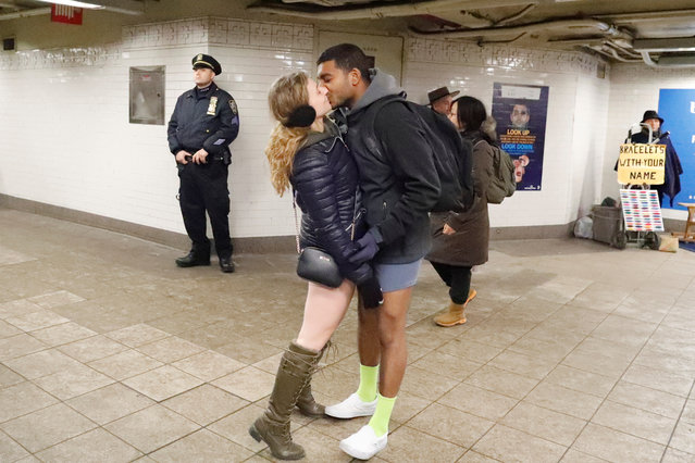 """A couple kisses during the annual """"No Pants Subway Ride"""" while a member of the New York City Police Department stands guard in New York City on January 7, 2018. (Photo by Elizabeth Shafiroff/Reuters)"""