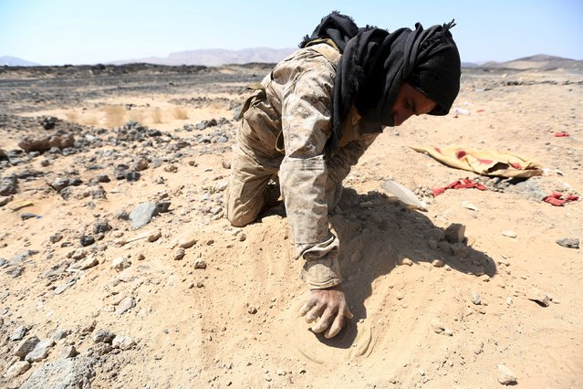 A tribal fighter loyal to Yemen's government removes a mine planted by Houthi militants at the frontline of an area controlled by the government, during their fight against the militants in the central province of Marib October 7, 2015. (Photo by Reuters/Stringer)