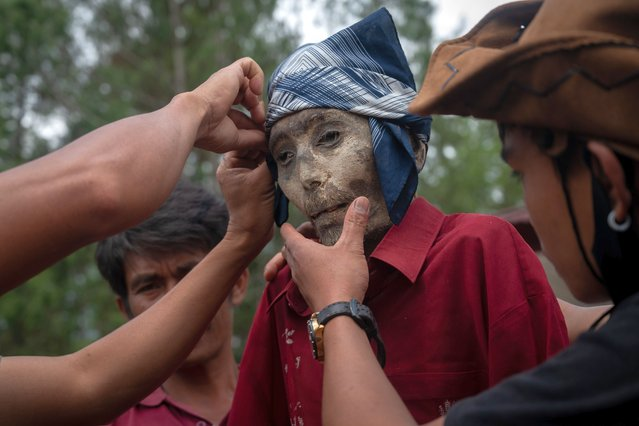 """Family members put on a new set of clothing on the preserved body of their relative during a traditional ritual called """"Manene"""" in Panggala, Nort Toraja, South Sulawesi, Indonesia, Tuesday, August 25th 2020. (Photo by Hariandi Hafid/ZUMA Wire/Rex Features/Shutterstock)"""