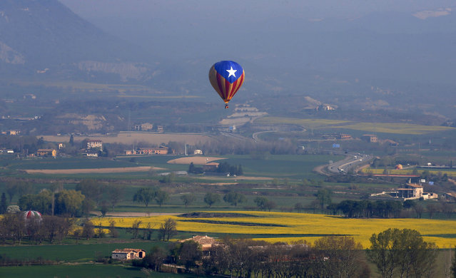 A hot air balloon decorated in the colours of the Catalan separatist flag, the Estelada, flies over the city of Vic, near Barcelona, during the XXXI International Mercat del Ram Balloon Trophy April 11, 201. (Photo by Albert Gea/Reuters)