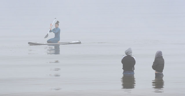Two people stand in the water in Melbourne's Port Phillip Bay as they watch a paddleboarder pass by in the fog on July 16, 2020. (Photo by William West/AFP Photo)