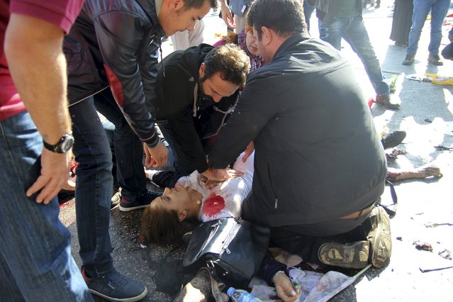 People try to help an injured woman after an explosion during a peace march in Ankara, Turkey, October 10, 2015. (Photo by Tumay Berkin/Reuters)
