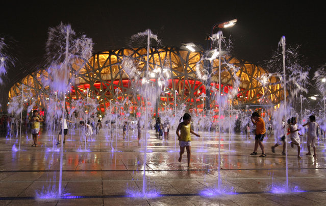 Children play in water fountains next to the National Stadium, also known as the Bird's Nest, during the Beijing 2008 Olympic Games. (Photo by Eric Gaillard/Reuters)