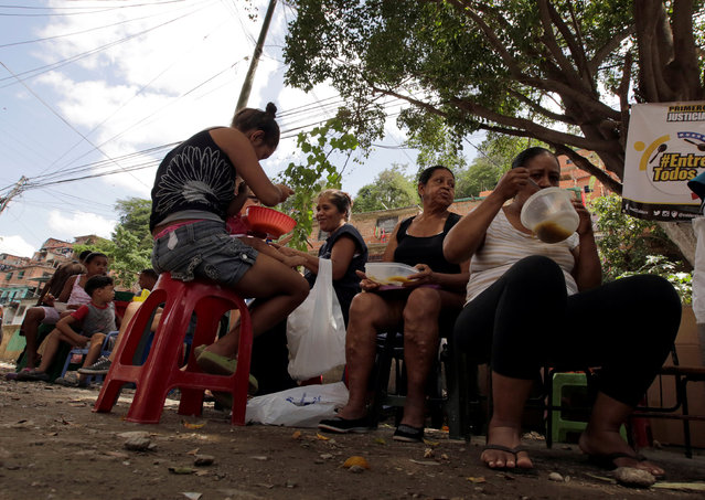 People eat free food which was prepared by residents and volunteers on a street in the low-income neighborhood of Caucaguita in Caracas, Venezuela September 17, 2016. (Photo by Henry Romero/Reuters)