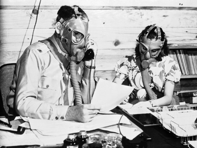 Capt. W. D. Smith of Greenville, S.C., Camp Blanding Chemical Warfare Service officer, trains in the use of the gas mask in Camp Blanding, Florida on August 19, 1942. Just to be sure that his office force could work under any conditions, he issued instructions that for an hour each day all work be done in gas masks to prove that conversations, even on the telephone and in dictation, could be carried on and other work done efficiently. (Photo by AP Photo)