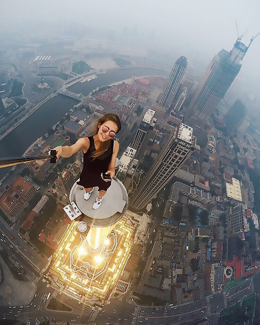 "An astonishing set of snaps of a thrill-seeker's sky-high catwalk show on the edge of some of the world's tallest buildings has turned her into a social media sensation. Daredevil Angelina Nikolau, 23, from Russia, has spent weeks travelling around China and Hong Kong posing for jaw-dropping skyscraper selfies hundreds of feet above the ground. Her vertigo inducing results – uploaded to Instagram – have made her an instant star on the internet. Angelina is described by Russian media as ""self-taught photographer, adventurer and roofer from Moscow"". Roofing – also known as rooftopping – is where people get as close as possible to the edge of a skyscraper's highest point to take selfies. (Photo by Kirill Oreshkin/CEN)"