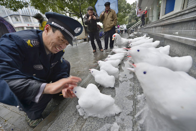 Security guard Du Jinqian makes snow birds on the steps in front of a bank where he works on February 19, 2013 in Hangzhou, China. Heavy snow hit large areas of east China on Tuesday. (Photo by China Foto Press)