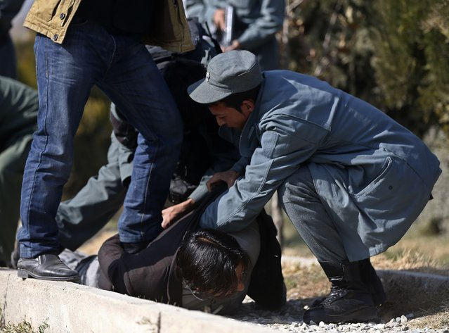 Security personnel arrest a suspect after a blast in Kabul, November 25, 2014. (Photo by Omar Sobhani/Reuters)