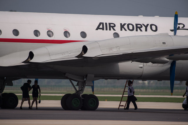 Crew members walk beneath an Air Koryo aircraft during the second day of the Wonsan Friendship Air Festival in Wonsan on September 25, 2016. (Photo by Ed Jones/AFP Photo)