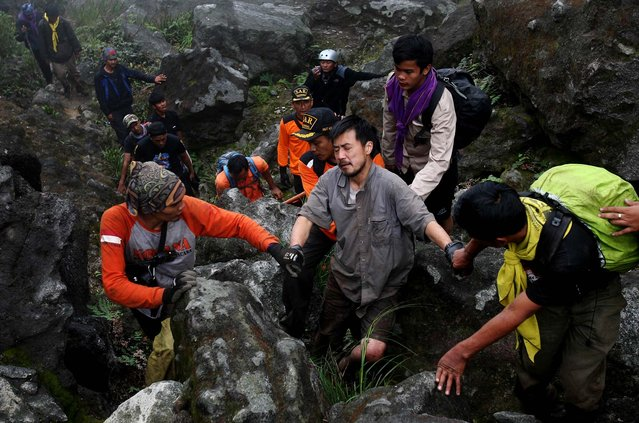 Japanese mountaineer Kosei Yamada, who was reported missing on Wednesday last week, is assisted by rescuers after he was found at the bottom of a ravine at Mount Sibayak in Karo, North Sumatra, Indonesia, on March 10, 2013. Yamada was found alive near the top of the 7,257 ft active volcano. (Photo by Binsar Bakkara/Associated Press)