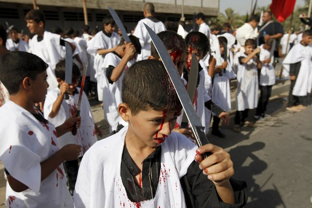 An Iraq Shi'ite Muslim boy bleeds as he gashes his forehead with a sword while commemorating Ashura in Baghdad, October 24, 2015. (Photo by Ahmed Saad/Reuters)