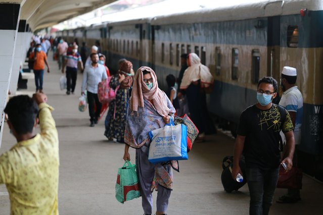 Passengers walk to board a train after Bangladesh Railway authority resume all operations in Dhaka, Bangladesh on September 16, 2020. (Photo by Rehman Asad/NurPhoto via Getty Images)