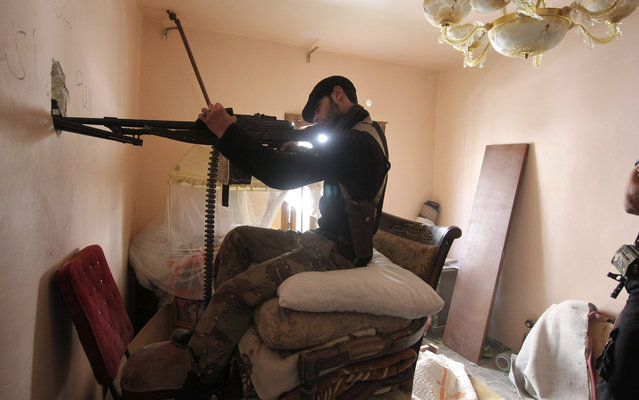 A Free Syrian Army fighter takes position inside a room as he points his weapon through a hole in Aleppo's Saif al-Dawla district March 20, 2013. (Photo by Giath Taha/Reuters)