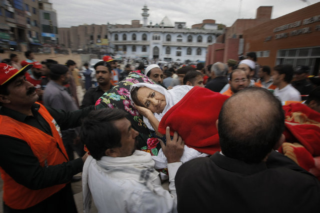 People rush an injured woman to a local hospital in Peshawar, Pakistan, Monday, October 26, 2015. (Photo by Mohammad Sajjad/AP Photo)