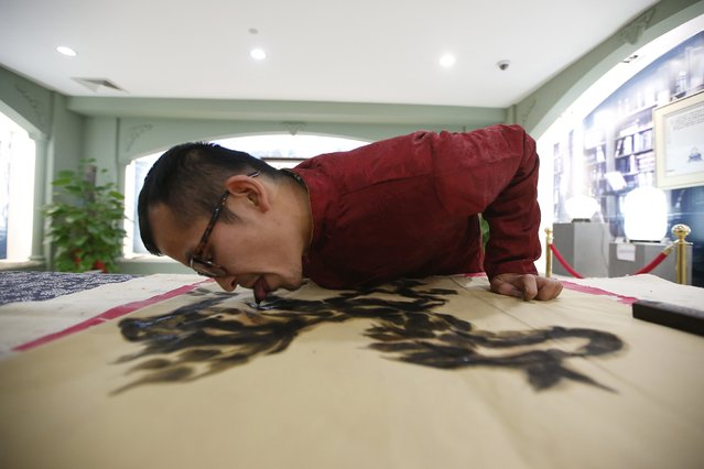 Folk artist Han Xiaoming demonstrates painting with his tongue in Hangzhou, Zhejiang province December 4, 2014. Han dips his tongue in ink to paint on paper, and uses his fingers to fill in final adjustments. The artist also uses a paintbrush held with his mouth and utilizes fish and vegetables as paint tools, local media reported. (Photo by Aly Song/Reuters)