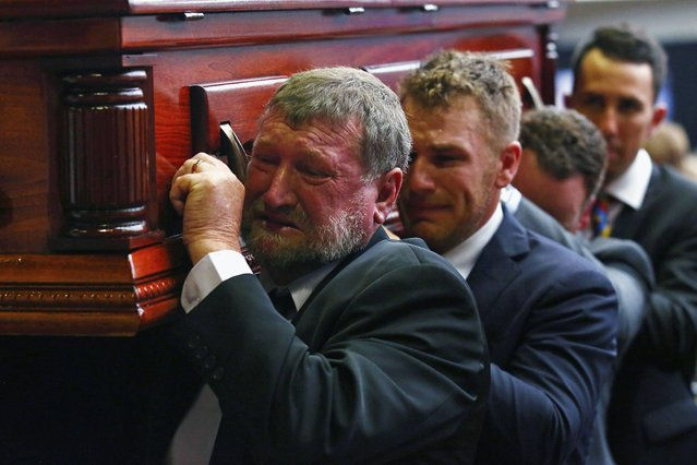 Gregory Hughes, left, father of Phillip Hughes, helps to carry Phillips's coffin during his funeral in Macksville, Australia, Wednesday, December 3, 2014. The funeral for cricketer Phillip Hughes turned into a celebration of his life on Wednesday despite the grief and sorrow still evident from his death. Hughes died last Thursday, aged 25, after being hit near the ear by a ball during a match between South Australia and his former state side New South Wales at the Sydney Cricket Ground. (Photo by Cameron Spencer/AP Photo)