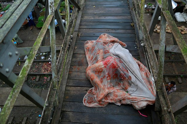 Men sleep covered with a mosquito net on a bridge above a train station outside Yangon, in this August 20, 2014 file photo. (Photo by Soe Zeya Tun/Reuters)