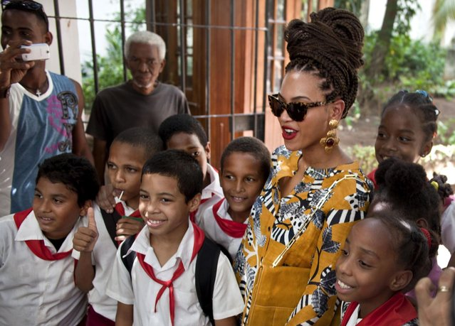 U.S. singer Beyonce poses for photos with school children as she tours Old Havana, Cuba, Thursday, April 4, 2013. Beyonce is in Havana with her husband, rapper Jay-Z, on their fifth wedding anniversary. (Photo by Ramon Espinosa/AP Photo)