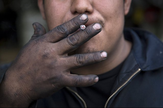 A worker smokes a cigarette in the Willets Point area of Queens in New York October 27, 2015. (Photo by Andrew Kelly/Reuters)