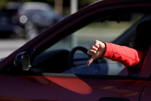 A person gives a thumbs down as she passes by Trump supporters on Election Day in Cobb County in Powder Springs, Georgia, U.S. November 3, 2020. (Photo by Chris Aluka Berry/Reuters)