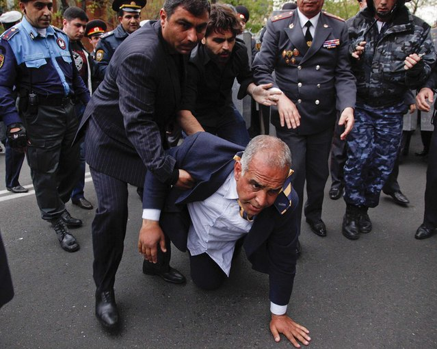 Armenian election runner-up Raffi Hovanessian is helped up after he fell during clashes between his supporters and police in Yerevan, on April 9, 2013. Armenian President Serge Sarkisian has been sworn in for another five-year term to lead the small former Soviet republic amid street protests by his opponents. (Photo by Tigran Mehrabyan/PanARMENIAN)