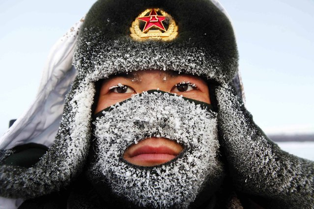 Frost covers the mask and part of the hat of a soldier of the People's Liberation Army (PLA) as he stand guard near the border of China and Russia in Heihe, Heilongjiang province December 10, 2014. The local temperature reached -32 degrees Centigrade (-25.6 degrees Fahrenheit) on Wednesday. (Photo by Reuters/Stringer)