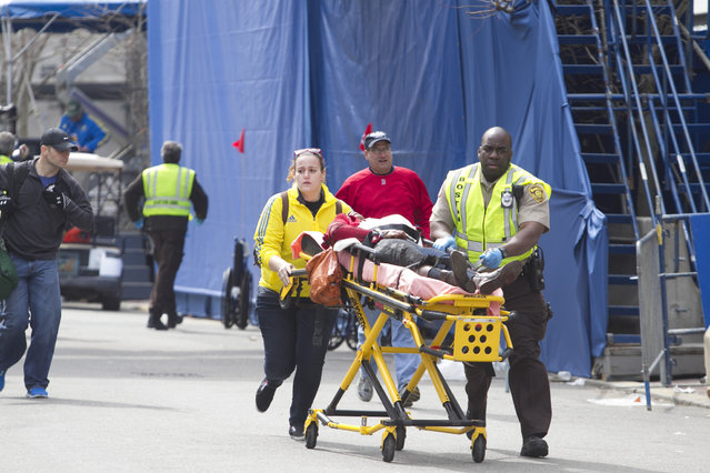 First responders transport the wounded where two explosions occurred along the final stretch of the Boston Marathon on Boylston Street in Boston, Massachusetts, U.S., on Monday, April 15, 2013. (Photo by Kelvin Ma/Bloomberg)