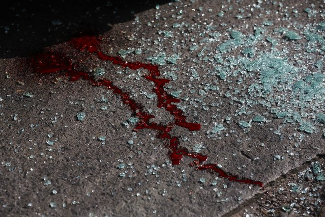 In this March 3, 2014 file photo, blood and shattered glass cover the pavement after gunmen opened fire on the driver of a passenger bus, Roger Enrique Hernandez Gutierrez, and his assistant, killing them both in Tegucigalpa, Honduras. Taxi and passenger bus drivers are targets of gangs seeking extortion money in this country with one of the highest murder rates in the world. (Photo by Dario Lopez-Mills/AP Photo)