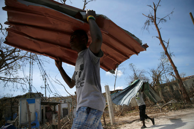 Men carry metal sheets near destroyed houses after Hurricane Matthew hit Jeremie, Haiti, October 10, 2016. (Photo by Carlos Garcia Rawlins/Reuters)