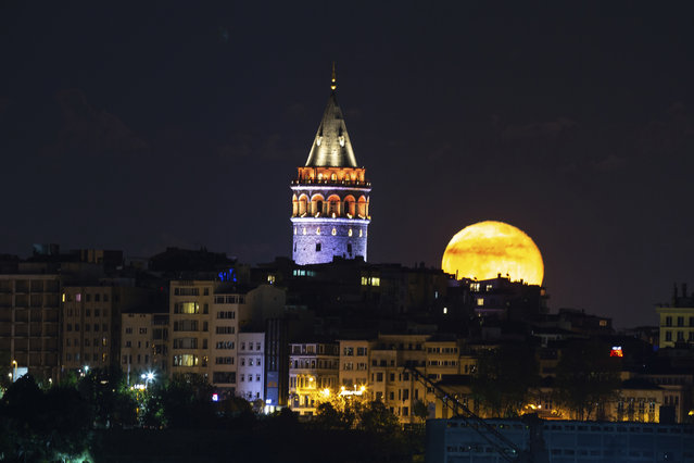 The moon rises over Istanbul's skyline with the iconic Galata Tower, Friday, May 8, 2020, a few hours before the start of a two-day curfew declared by the government in an attempt to control the spread of coronavirus. The full moon, also known as the supermoon or Flower Moon, was visible on Thursday, May 7. (Photo by Emrah Gurel/AP Photo)