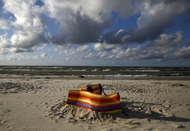 A couple sunbath on the beach in Ostrowo, northern Poland, July 20, 2015. Picture taken July 20, 2015. (Photo by Kacper Pempel/Reuters)